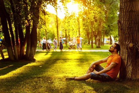 A happy thoughtful dreamer man is sitting on green grass in a park at sunny summer day and looking into future. Concept of relaxation, wellbeing, lifestyle.
