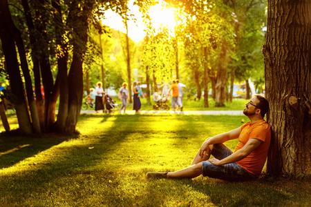 Un feliz hombre reflexivo soñador está sentado en la hierba verde en un parque en el día soleado de verano y mirando hacia el futuro. Concepto de relajación, bienestar, estilo de vida. Foto de archivo