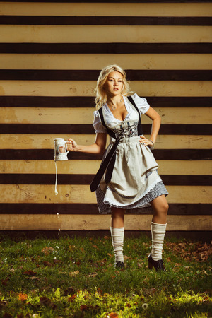 german girl: A beautiful young german girl in dirndl clothing is holding a jug of beer at Oktoberfest.