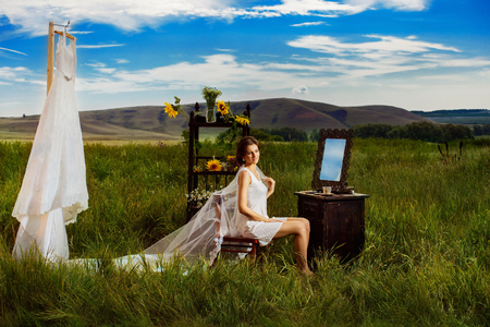 Concept of bride morning. Beautiful bride is sitting outdoors at amazing summer rural landscape background with green grass field, sunflowers and wedding dress on rack. Standard-Bild