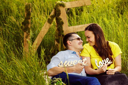 happy couple: Beautiful happy couple is holding wooden caption Sweet Love and laughing at green summer grass background. Stock Photo