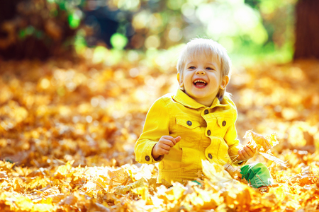 young leaves: Little happy boy in yellow jacket is playing with leaves at golden autumn park background.