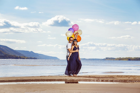 wedding couple: Happy young pair with bright balloons is having fun at summer beach background.