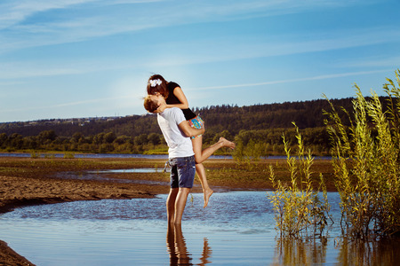 prety: Happy man is holding prety young girlfriend on hands outdoors at summer beach background at their dating.