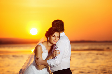 Beautiful bride is  emracing elegant groom during their wedding travel at golden tropical summer sunrise view.