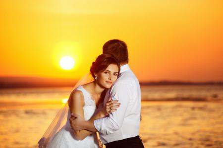 Beautiful bride is  emracing elegant groom during their wedding travel at golden tropical summer sunrise view.