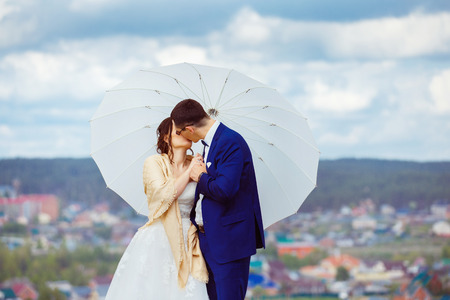 blue summer sky: Young happy wedding couple with white umbrella is kissing at hill top at blue sky view background.