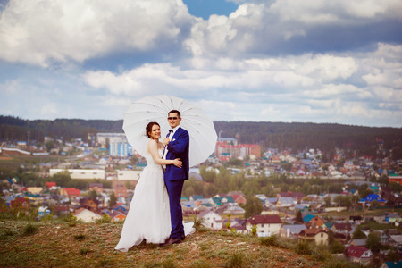 happy couple white background: Young happy wedding couple with white umbrella is emracing at hill top at blue sky view background. Stock Photo