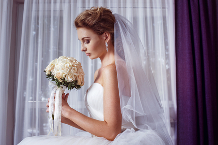 bride bouquet: portrait of beautiful young bride holding roses wedding bouquet at white curtain background. Stock Photo