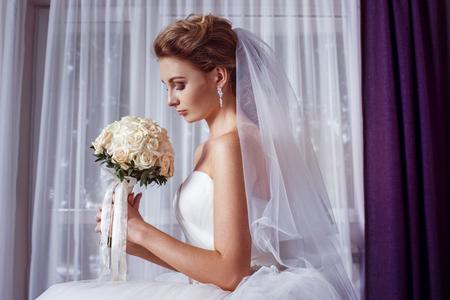 retrato de la hermosa boda ramo de rosas joven novia que sostiene en el fondo cortina blanca.