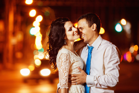 tenderly: Elegant dressed man is tenderly embracing happy laughing woman at bright night street lights background. Stock Photo
