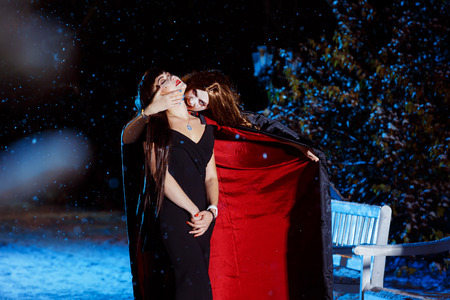 Beuatiful female vampire in long pallium is biting her victim at blue light cold winter evening background.