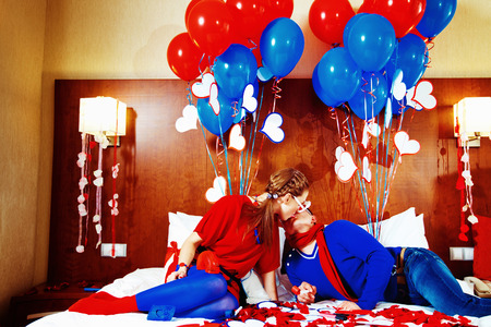 flying kiss: Happy couple dressed in red and blue are kissing on bed with colorfull balloons at background. Stock Photo