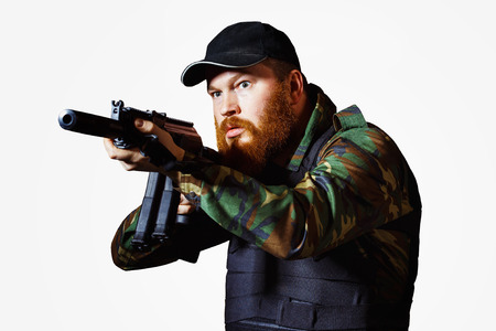 cruel: Terrorist in camouflage with red beard and cruel face is holding rifle isolated at white background.