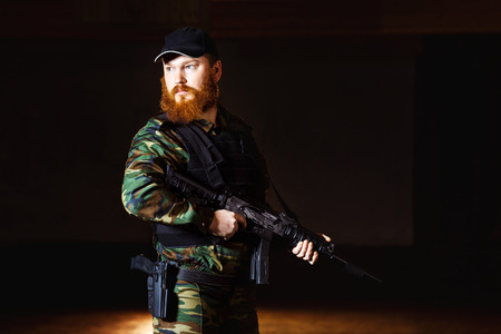 attacker: Terrorist in camouflage with red beard and cruel face is holding rifle at indoors background. Stock Photo