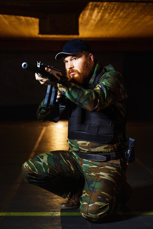 cruel: Terrorist in camouflage with red beard and cruel face is holding rifle at indoors background. Stock Photo