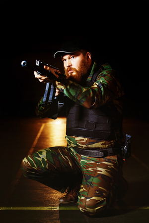 cruel: Terrorist in camouflage with red beard and cruel face is holding rifle at dark background.