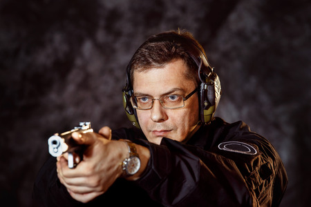 9mm: Closeup portrait of man with gun selecting aim at training club at dark background.