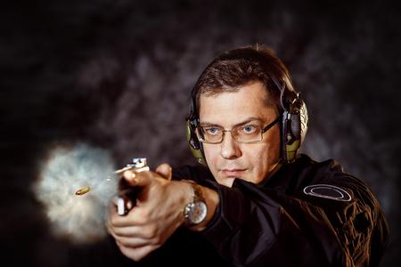 Closeup portrait of man with gun making shot at training club at dark background. Stock Photo