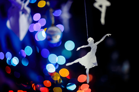 silhoette: Christmas colourfull blurred lights background with a paper dancer silhoette.
