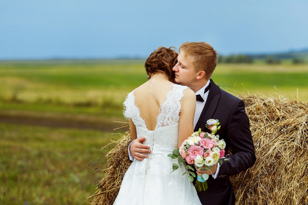 Beautiful young bride is tenderly embracing husband at rural haystacks summer field background.