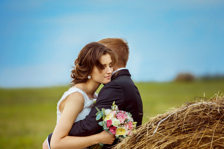 Beautiful young bride with closed eyes is tenderly embracing husband at rural haystacks summer field background. Stock Photo