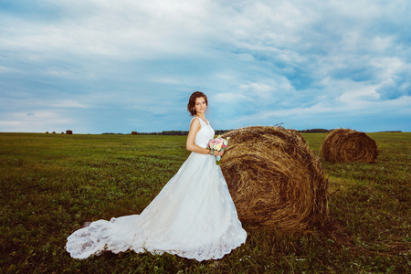 Portrait of beautiful young bride in georgeous white dress at summer field with golden haystacks background.
