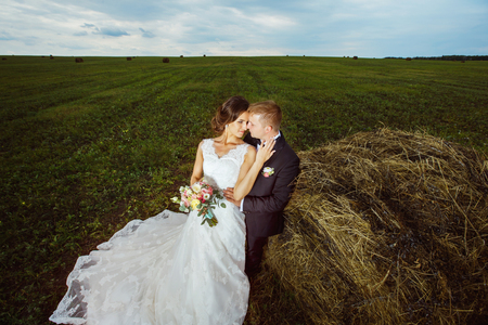 tenderly: Beautiful young bride is tenderly embracing husband at rural haystacks summer field background.