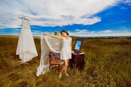 Concept of bride morning. Beautiful bride is standing outdoors holding veil at amazing summer rural landscape field background with sunflowers decoration and wedding dress on rack.