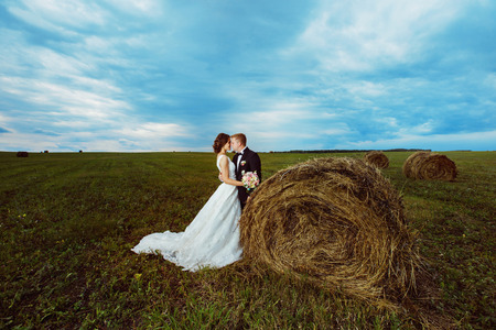 tenderly: Beautiful young bride is tenderly kissing husband at rural haystacks summer field background.