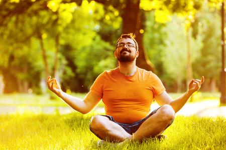 Portrait d'un homme heureux avec une barbe méditant dans un parc à été coucher de soleil doré fond naturel. Banque d'images