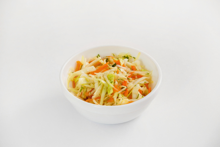Bowl of fresh healthy diet salad of coleslaw with carrot and oil isolated at white background.