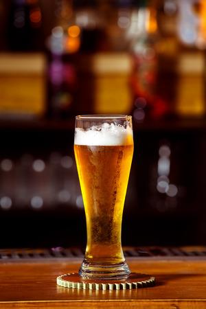 unbottled: Closeup image of glass with golden unbottled light beer at bar background.