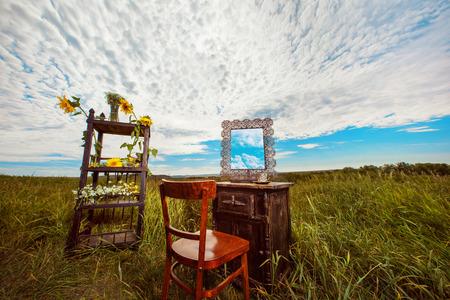 Hermoso paisaje rural de campo con muebles vintage decorado con flores silvestres en el fondo del cielo nublado de verano.