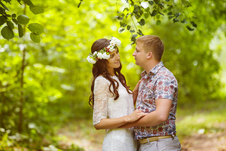 circlet: Beautiful young girl with flowers circlet is embracing boyfriend at green outdoors spring background.