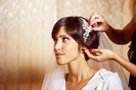 Closeup portrait of bridal morning preparation ceremony. Stylist is putting on diadem.