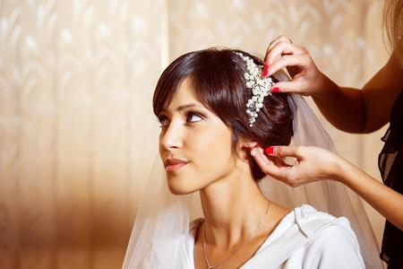 Closeup portrait of bridal morning preparation ceremony. Stylist is putting on diadem.