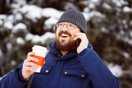 outdoorsman: Happy bearded hipster man in glasses with cup of hot coffee is talking by cellphone outdoors at winter snowy background.