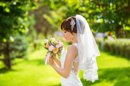 amazing stunning: Beautiful bride is smelling wedding bouquet standing at green summer park background. Stock Photo