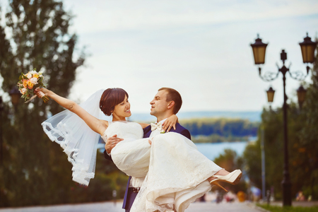 whirling: Happy elegant man is whirling his pretty wife at summer city street background. Stock Photo