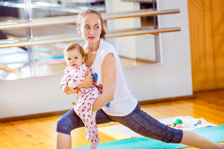 Closeup portrait of mom and baby making fitness exercises at gym background. Stock Photo