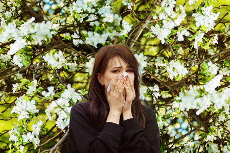 Portrait of sick sneezing woman at spring outdoors blossoms background.