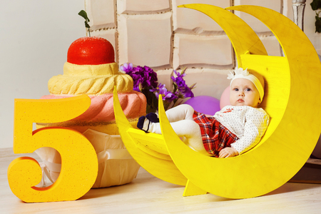 five month old: Portrait of little cute five month old child near at big cake background.
