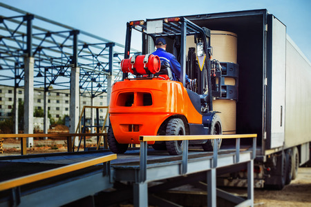 warehouse equipment: Forklift is putting cargo from warehouse to truck outdoors