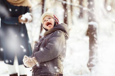 palle di neve: Ritratto di ragazzo felice in giacca e cappello di gioco palle di neve all'aperto in inverno foresta sfondo. Archivio Fotografico