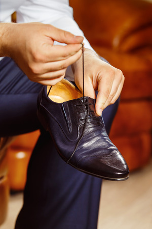 workday: Close up image of a man who is preparing for his workday and tying a shoe lace.