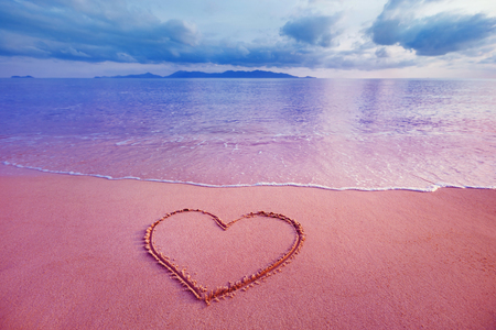 Closeup image of heart symbol written on sand at pink sea sunrise background. Stock Photo