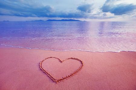 Imagen de detalle de símbolo del corazón escrito en la arena en el fondo rosado amanecer de mar. Foto de archivo