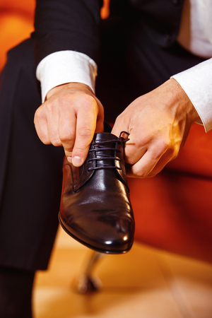 workday: Close up image of a businessman who is preparing for his workday and tying a shoe lace.