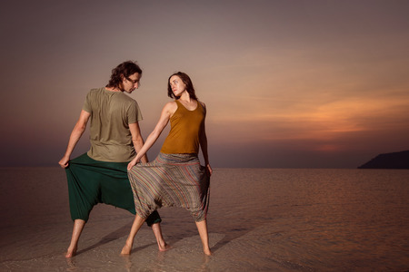 long pants: Beautiful young couple is standing at golden sea sunset background and holding long pants.